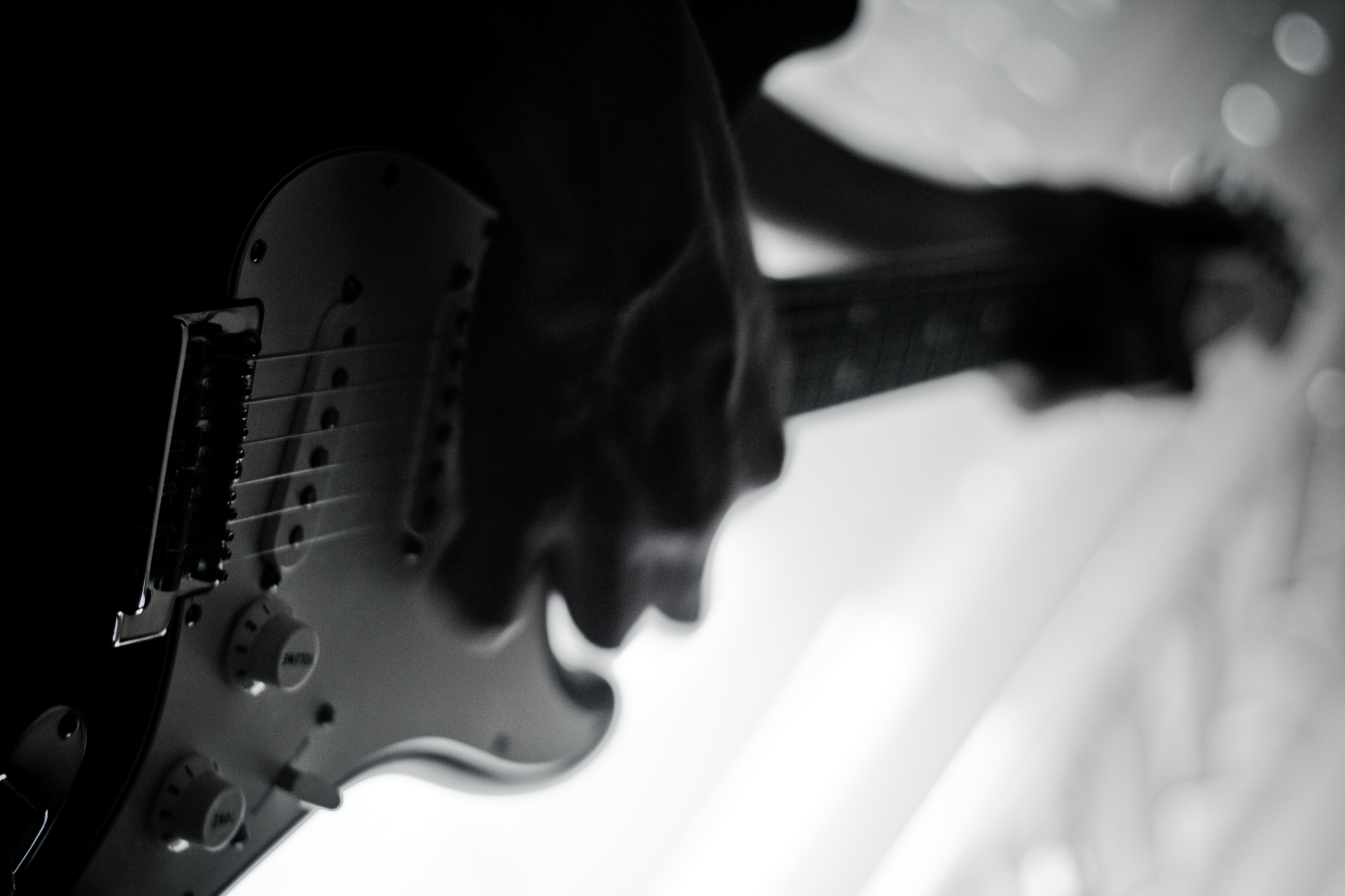 A low-angle black-and-white shot of a person playing an electric guitar