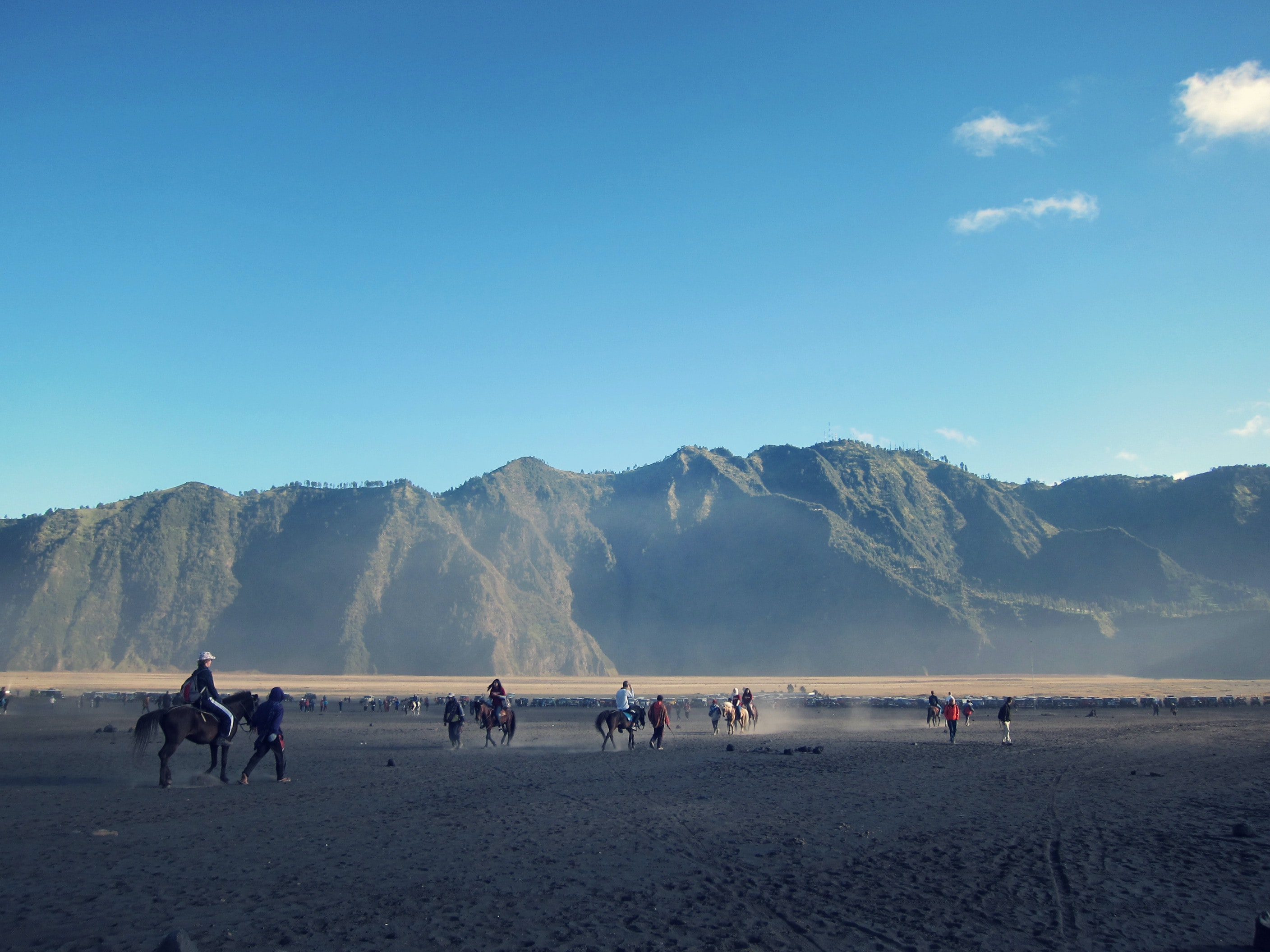 A plain at the foot of a mountain range with people on horseback and on foot