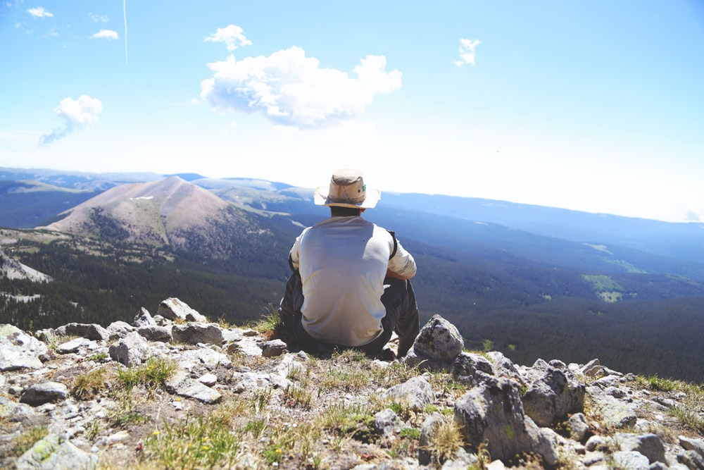 person sitting on a gray rock watching over a mountain