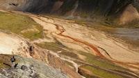 bird's eye view of man standing on gray mountain