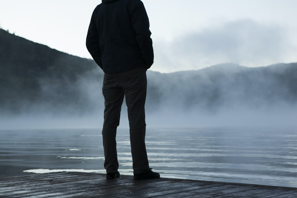 man standing facing body of water under white sky