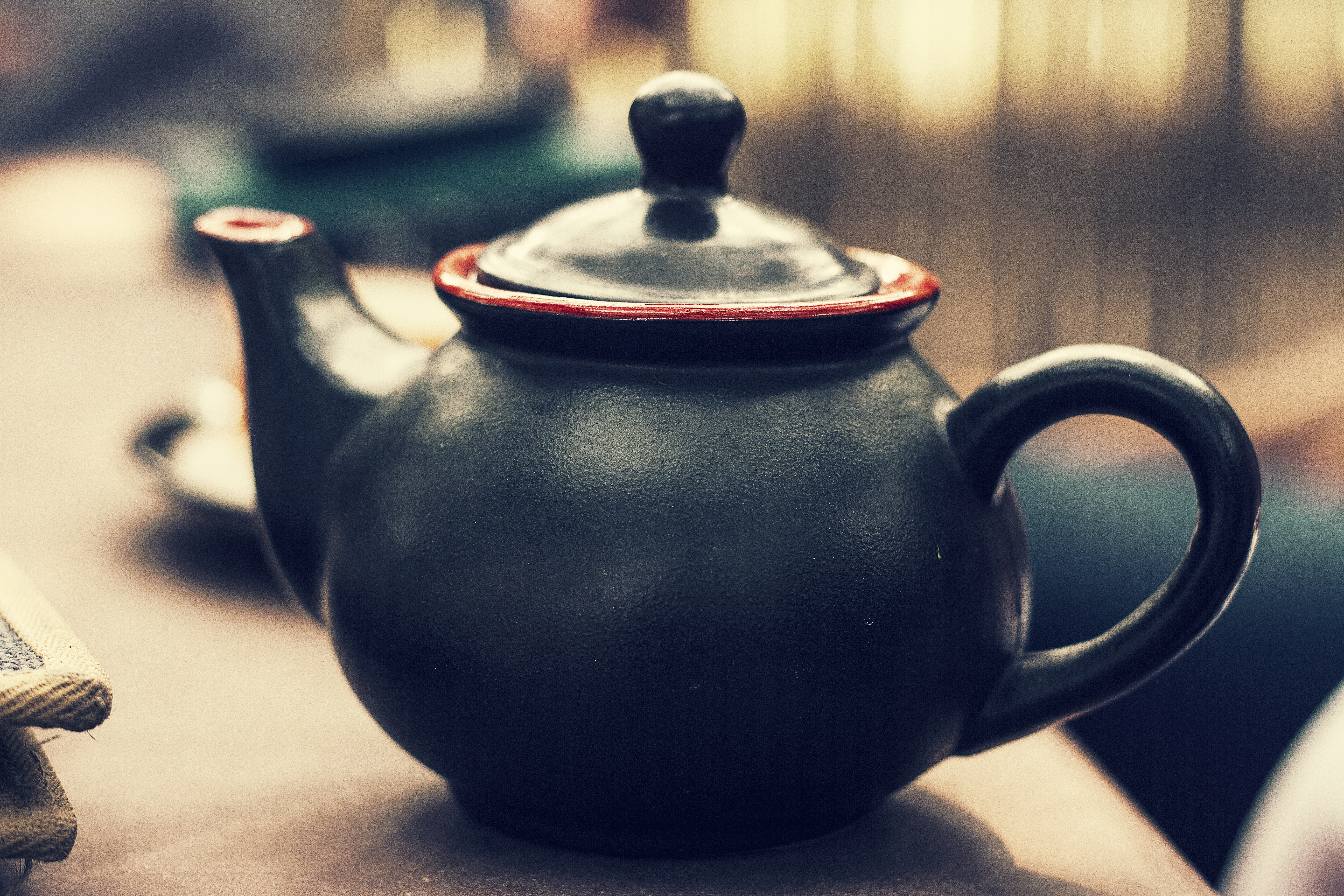 Black and red ceramic tea kettle with a handle and blurry background