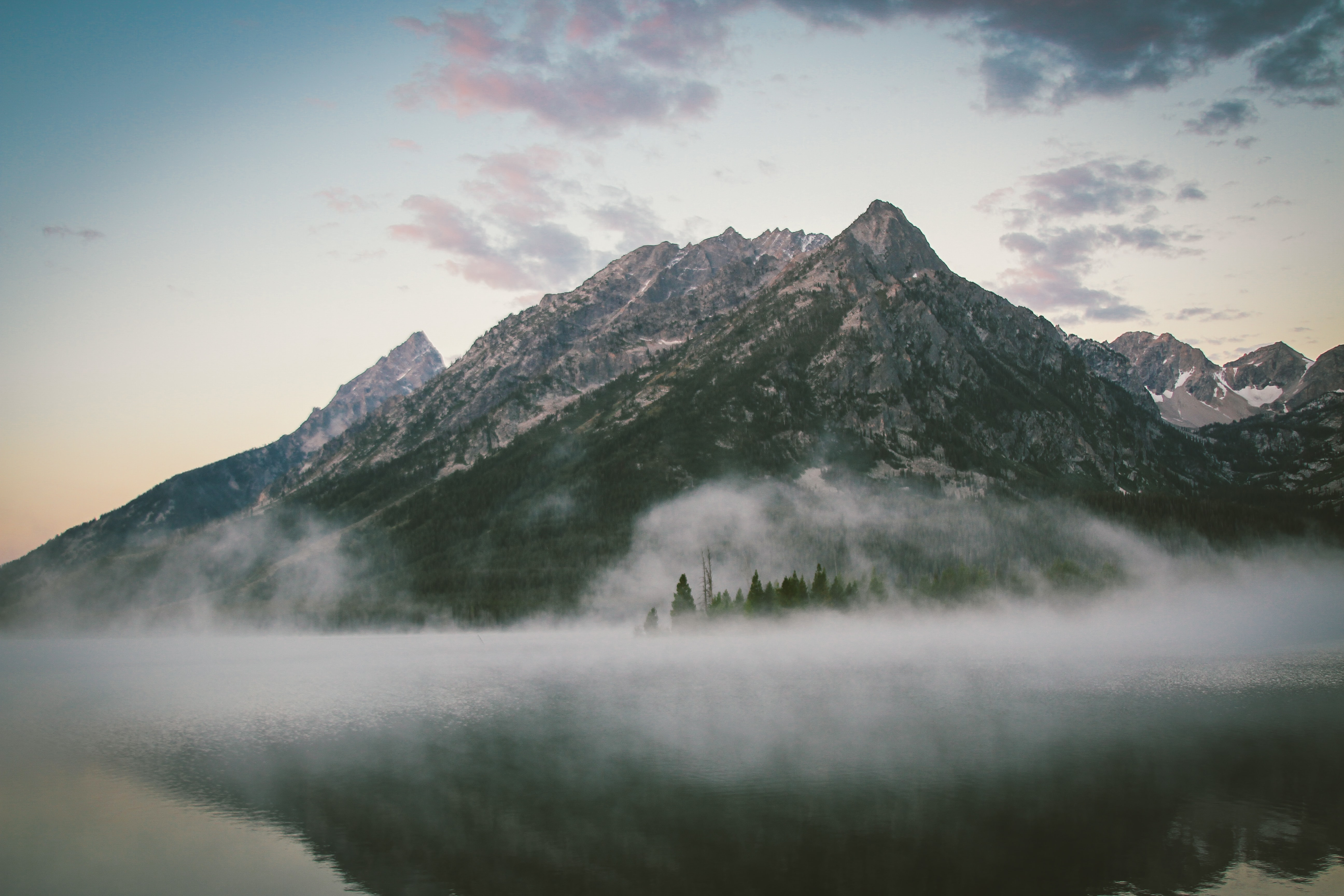 A majestic mountain peak with a mist at its foot towering over the calm surface of a lake