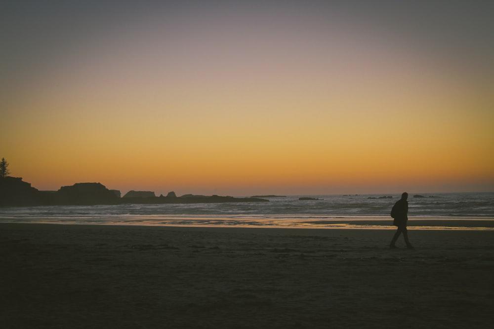silhouette of person walking on seashore