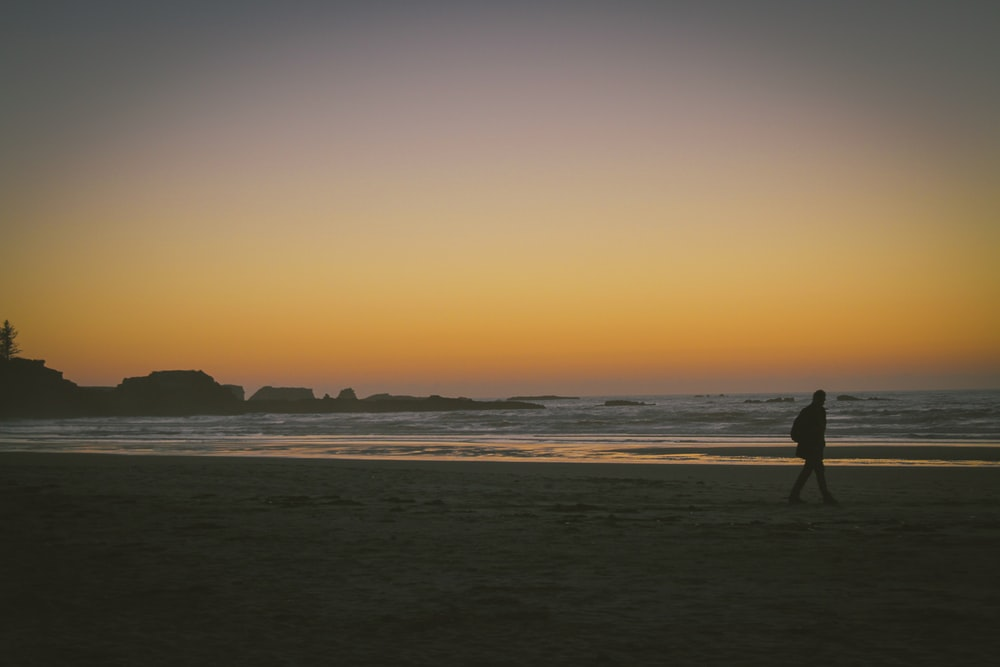 silhouette of person walking on seashore