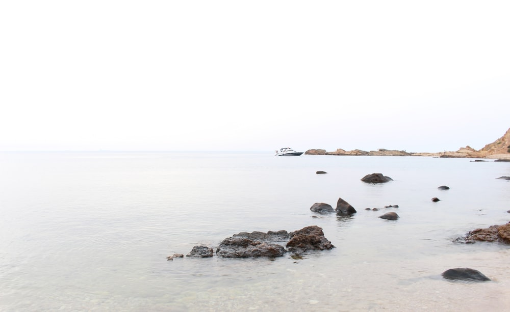 body of water near rocks at daytime