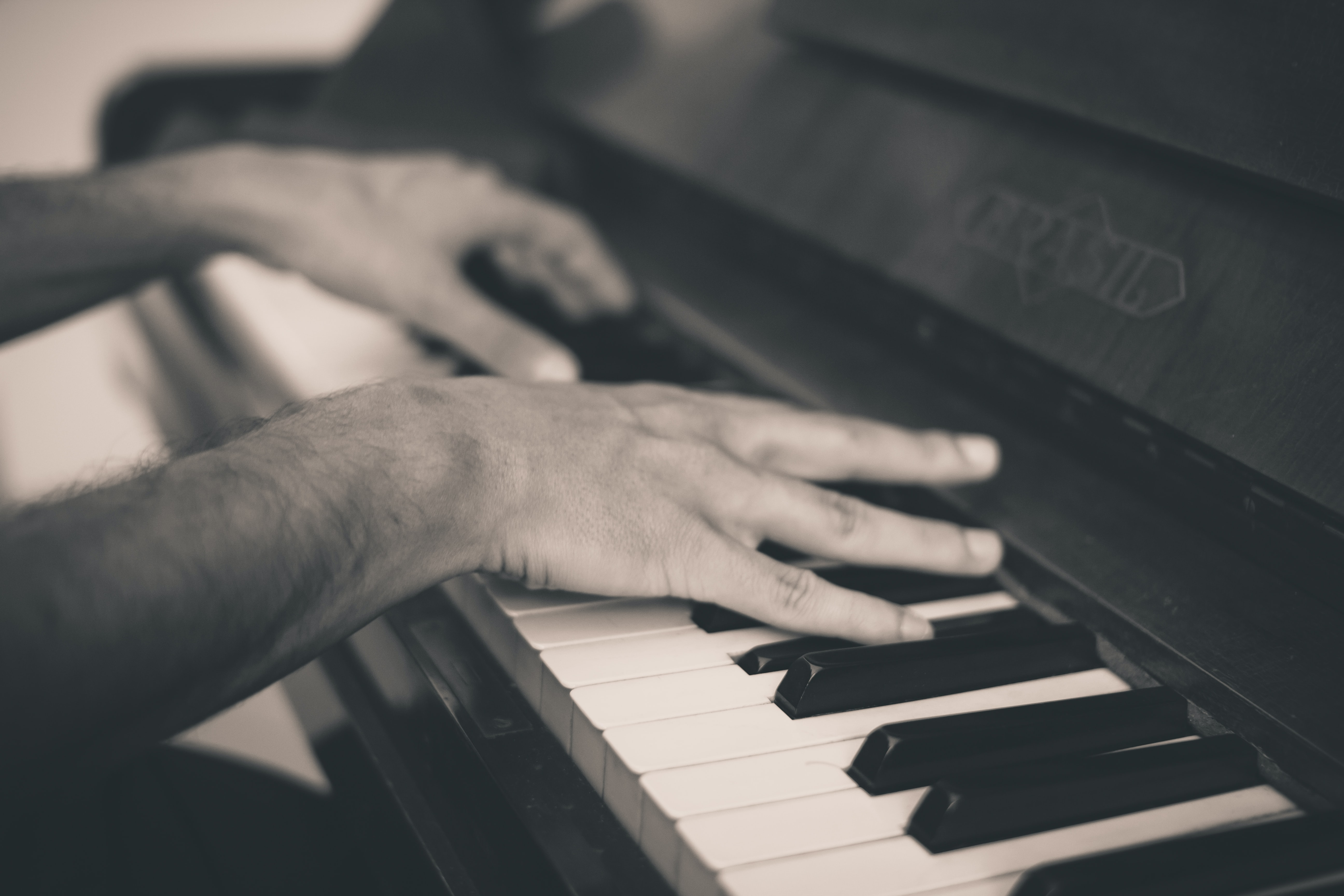 A black-and-white shot of a man's hands playing the piano