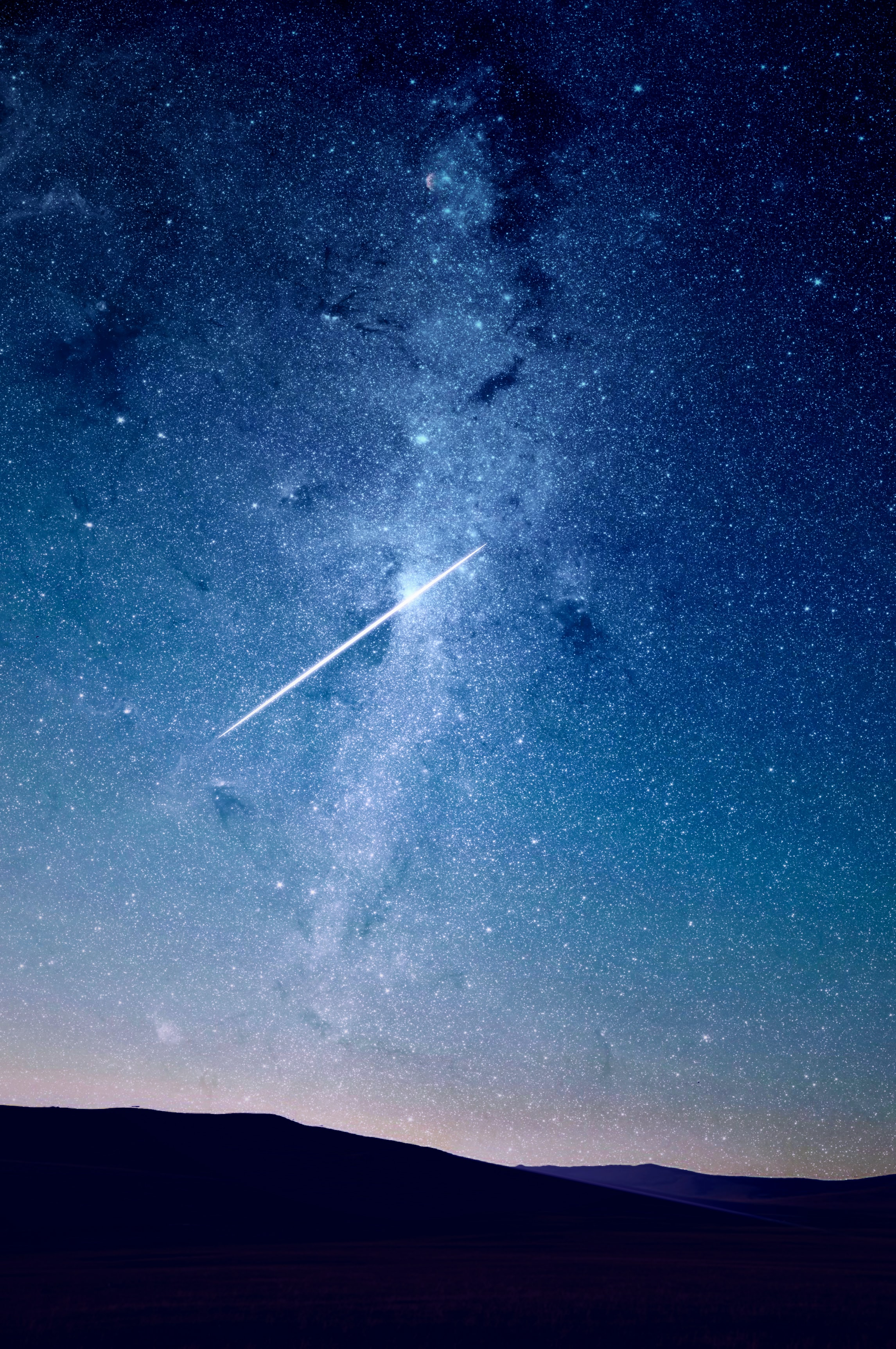 Aerial view of the stars and a shooting star in the sky at night.