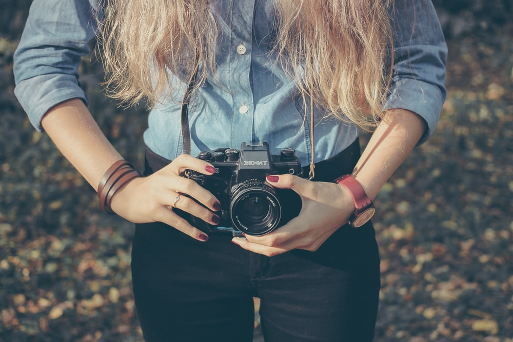 photo of woman holding MILC camera