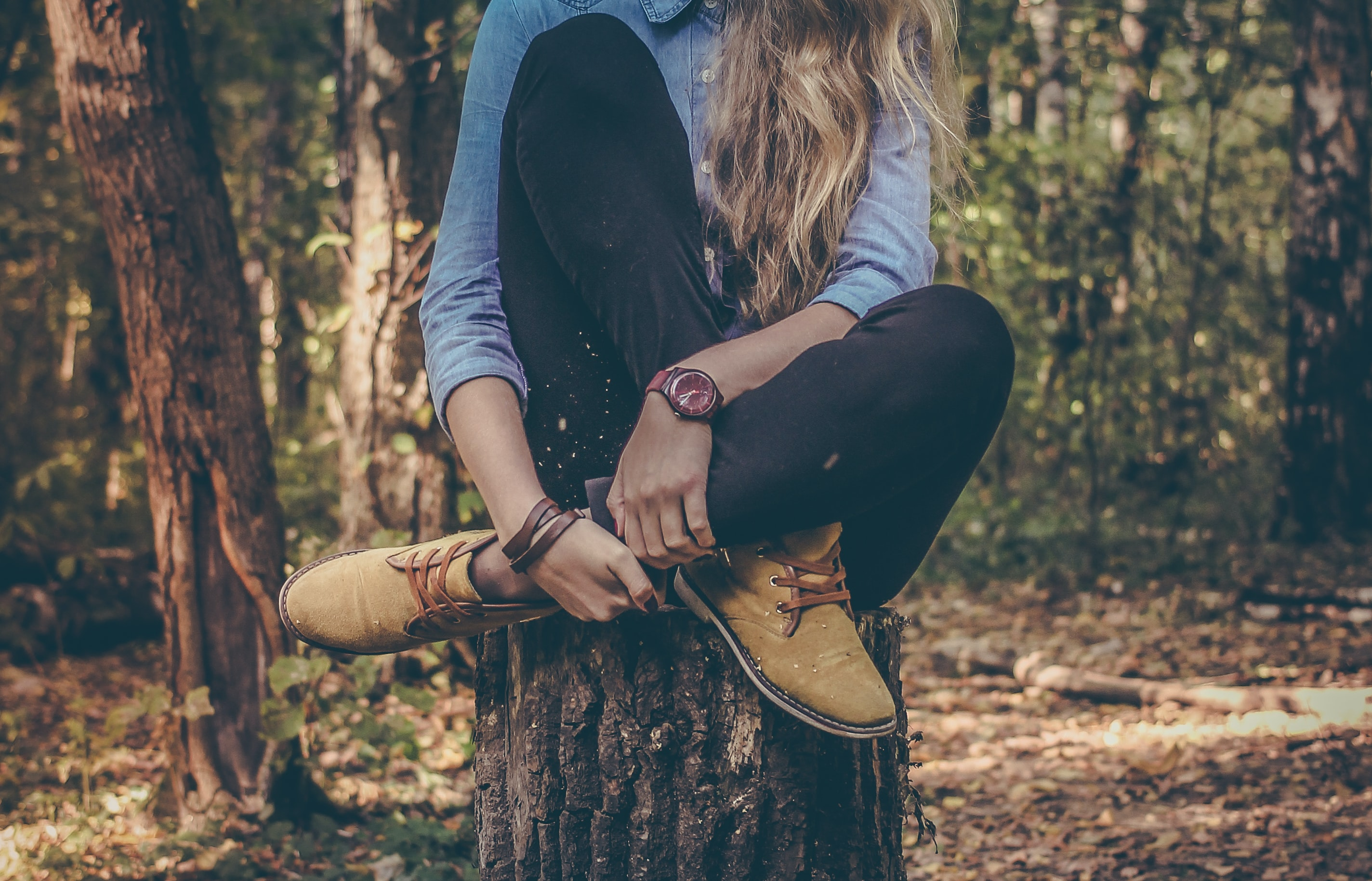 Woman wearing watch sitting on tree stump in the forest wearing boots