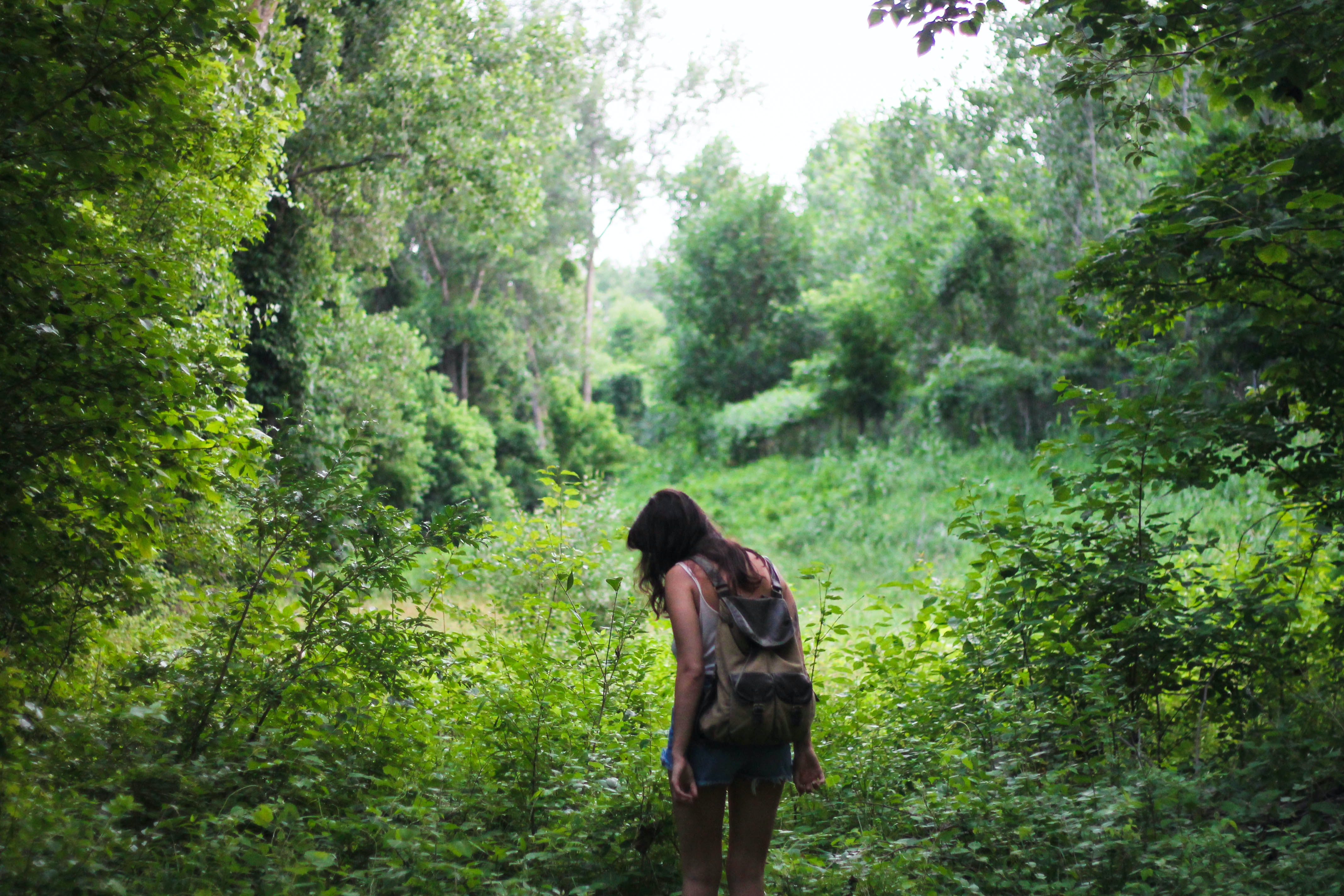 A dark-haired woman with a backpack hiking among green trees and bushes