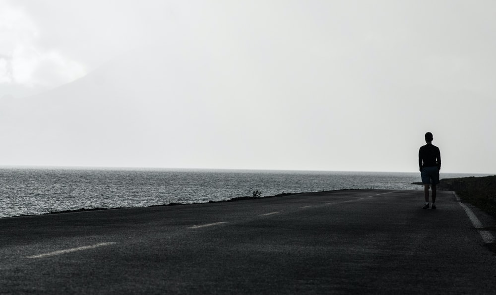 man standing on asphalt road beside body of water under gray sky