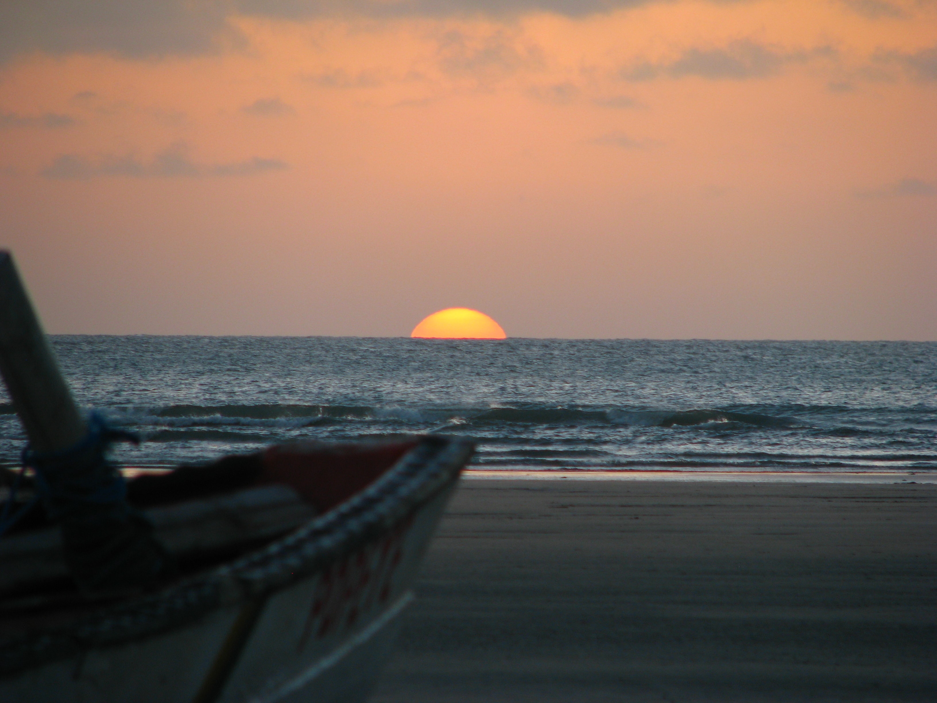 The golden sun resting on the horizon at sea with a fishing boat in the foreground