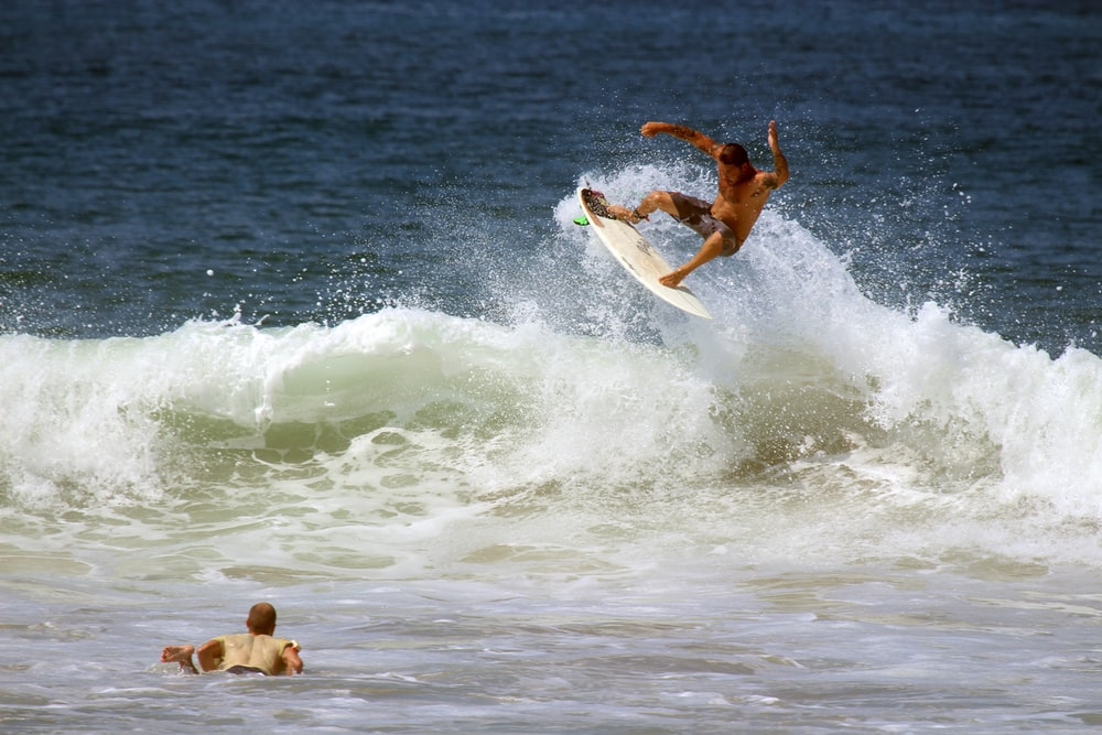 man surfboarding on ocean wave during daytime