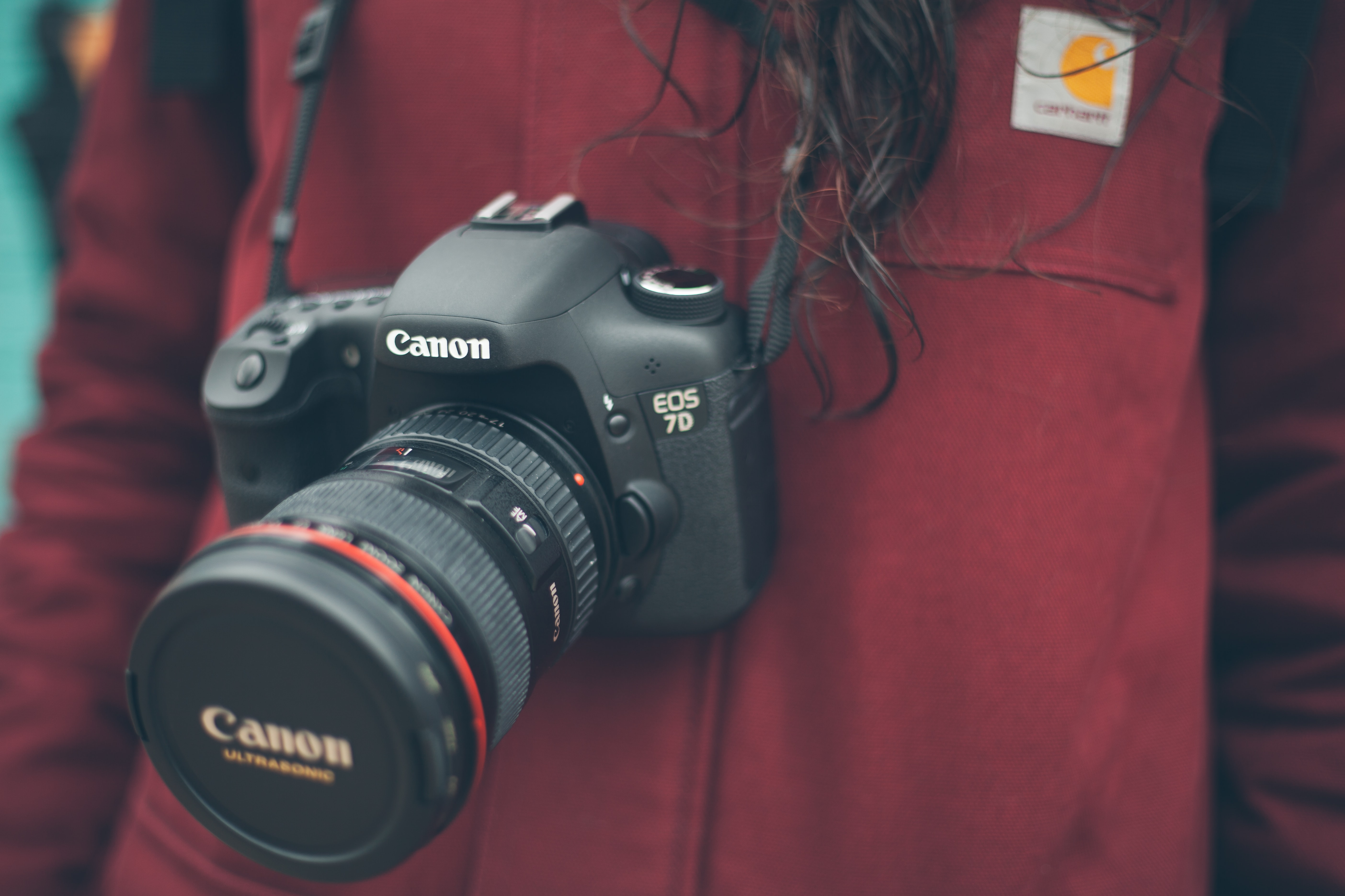 A woman photographer on a red outfit handing a black canon digital camera around her neck