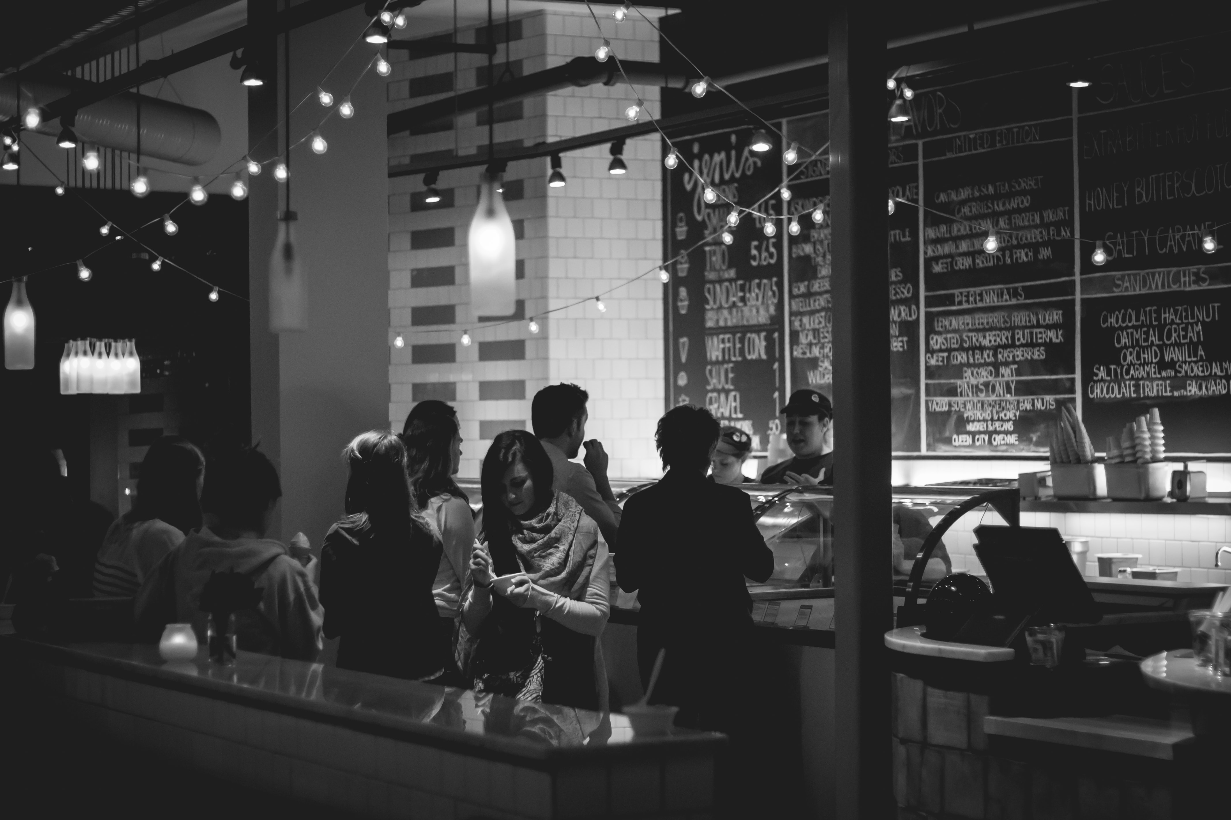 A black-and-white shot of young people near the counter in a café