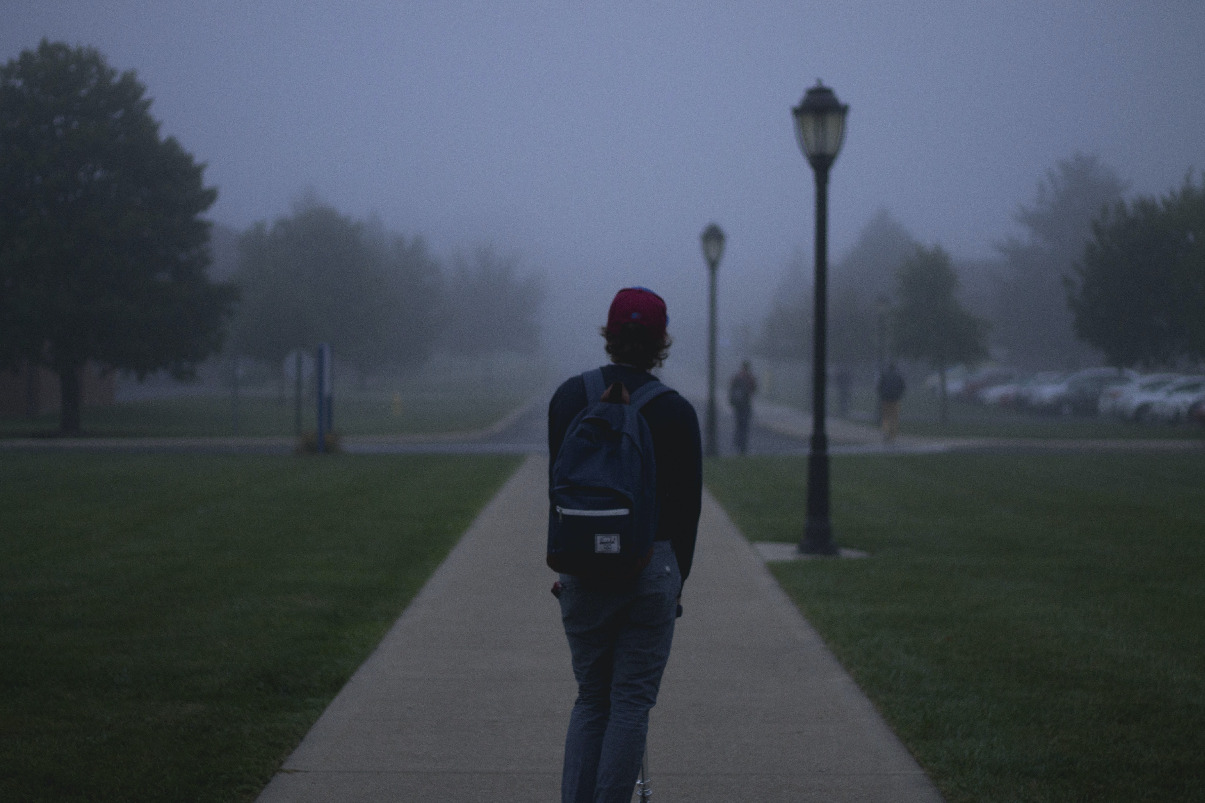 College student alone on a razor scooter on a foggy day