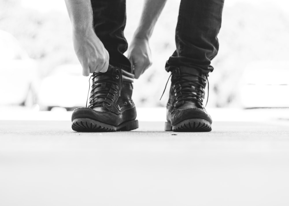 person wearing black leather lace-up boots