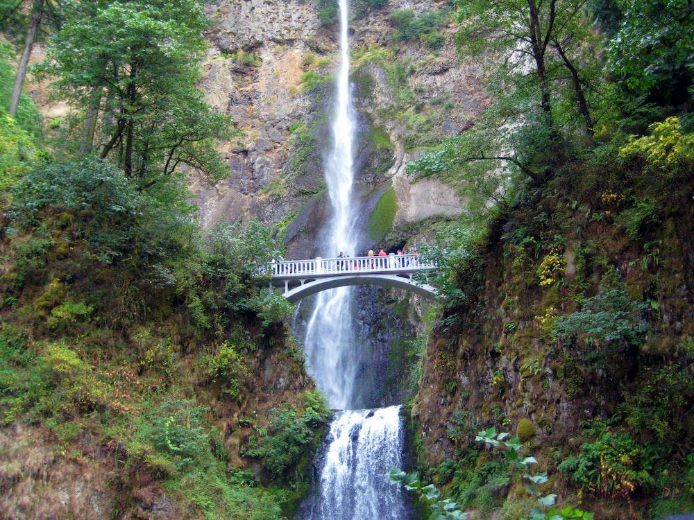white bridge in front of waterfalls during daytime