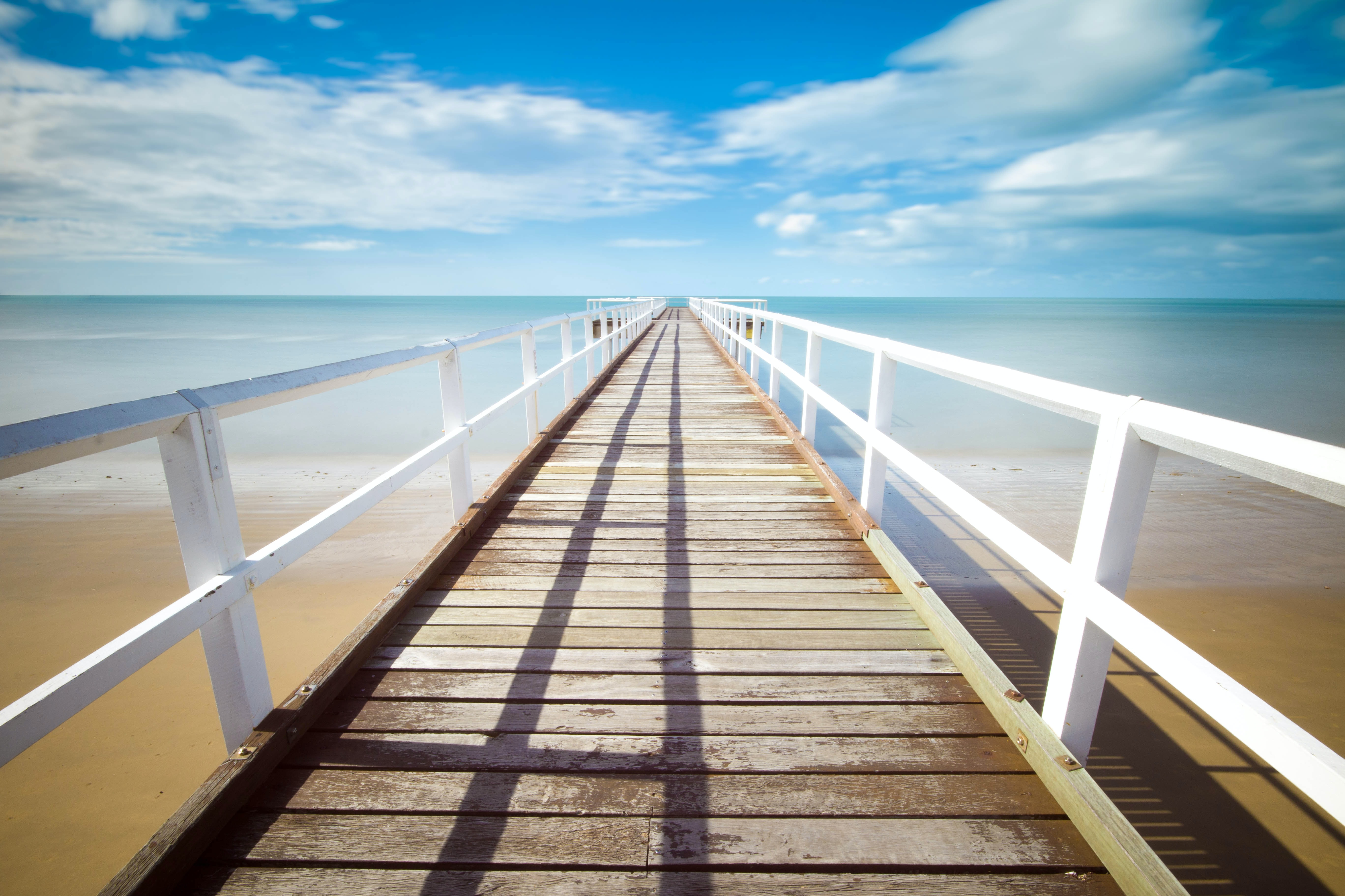 Wooden pier pathway with white wooden railing