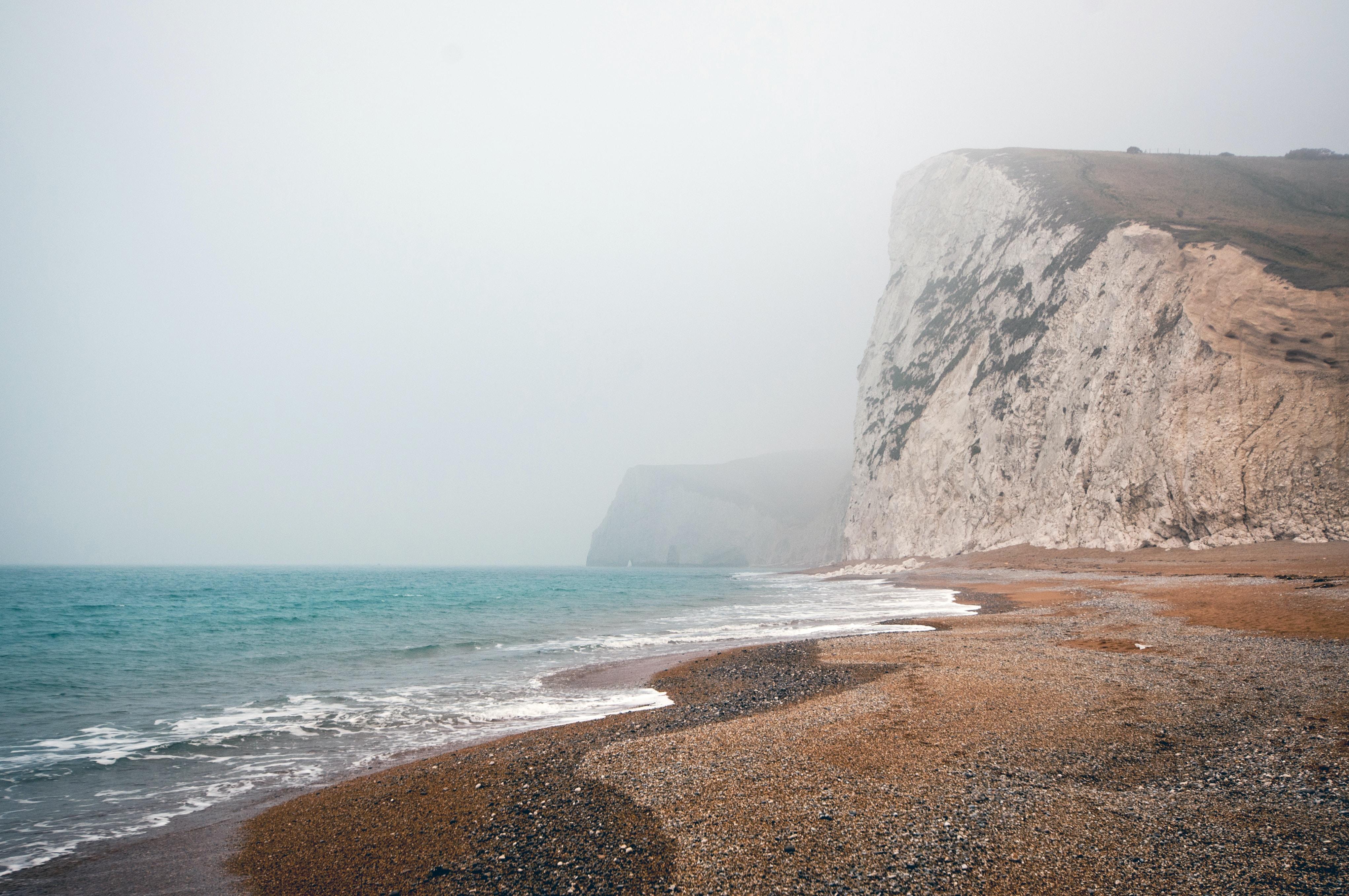 Bluffs line the seashore of a foggy ocean beach