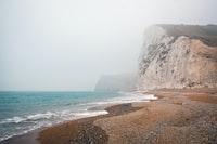 gray rock mountain near body of water at daytime