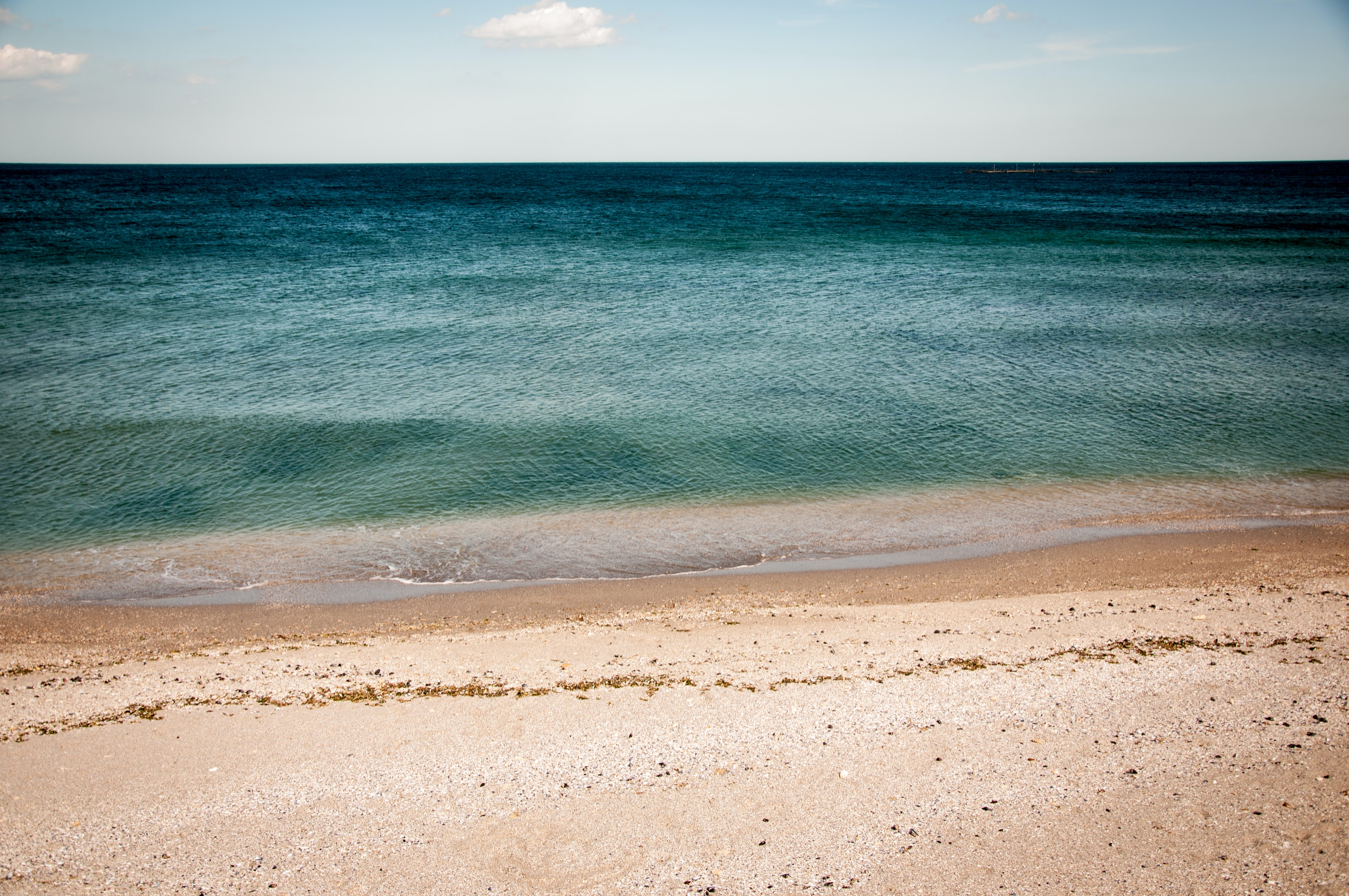 complete beach view of the shore and blue inviting ocean