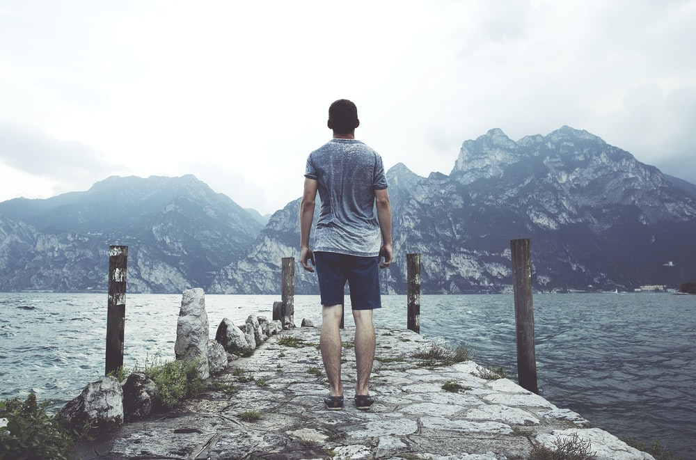 man standing on gray concrete dock facing body of water and mountains at daytime
