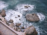 rock formations with crashing seashore at daytime