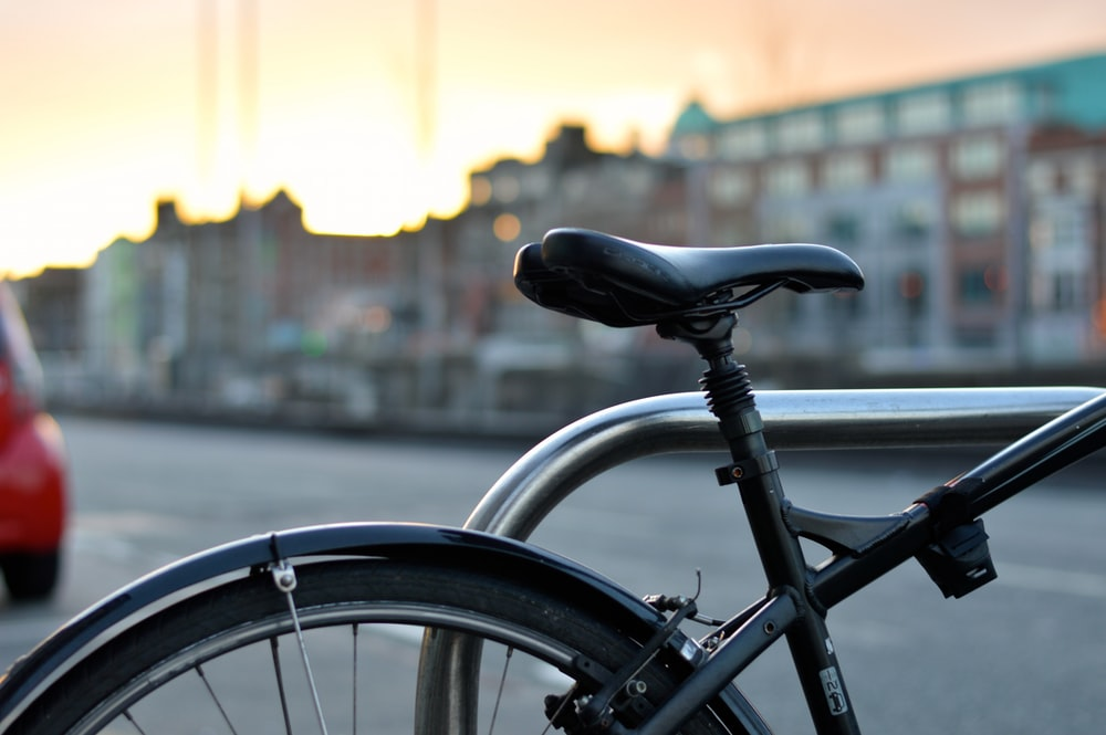 The wheel and seat of a bicycle at sunset