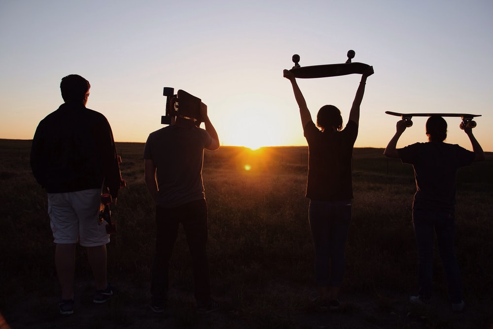 group of people holding skateboards under sunset