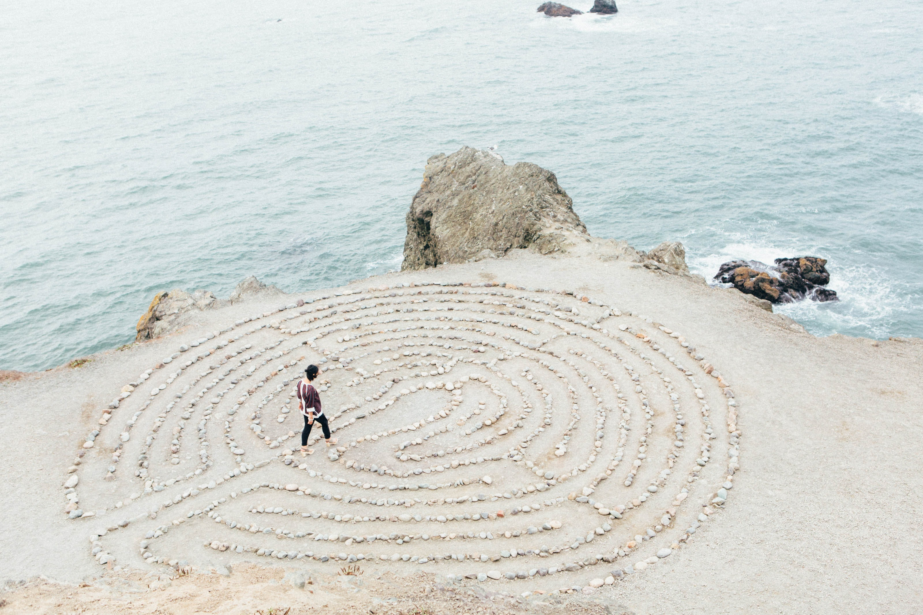 A person walking through a maze made out of rocks by the side of the beach