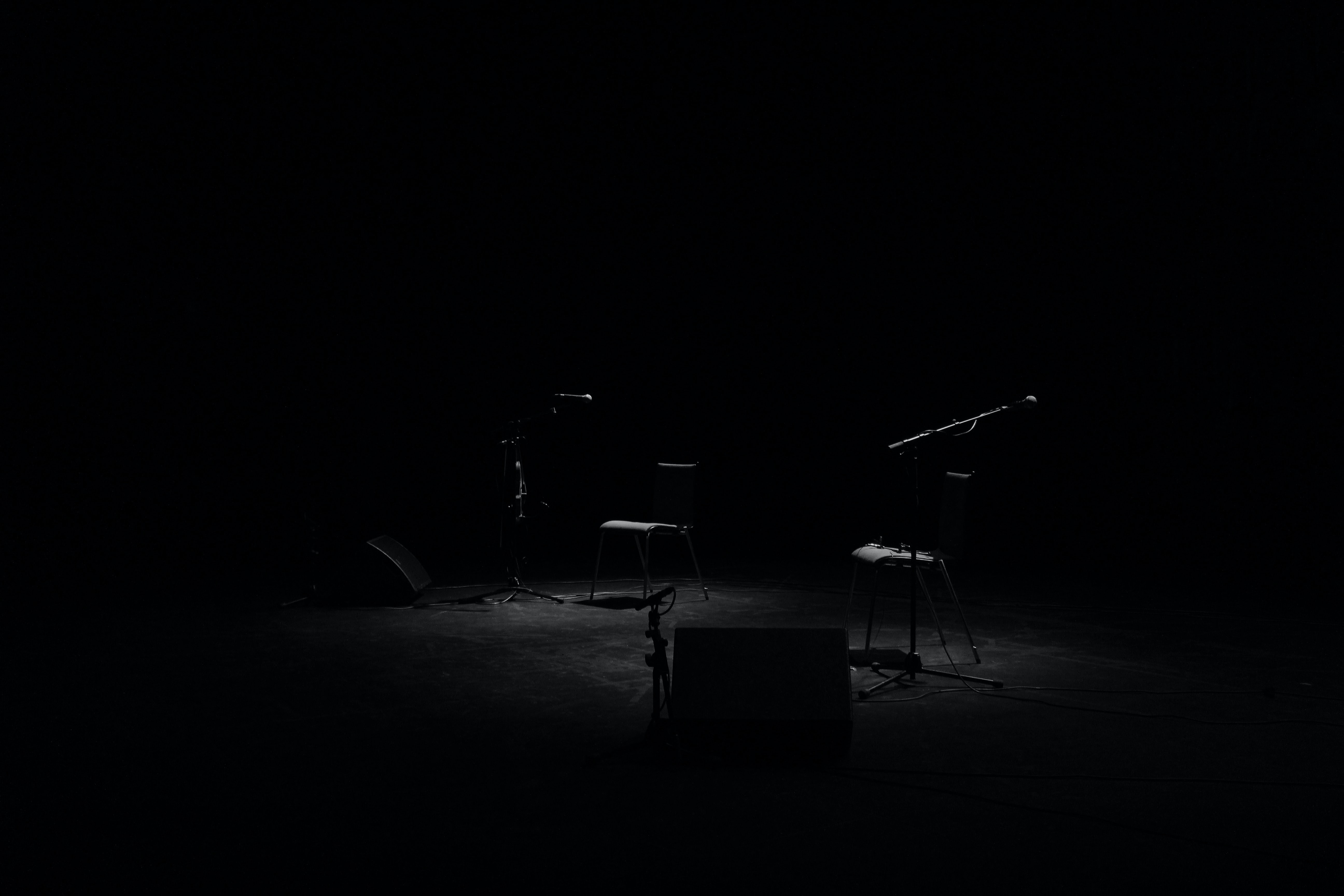 A Dim Shot Of Two Chairs And Microphone Stands On An Empty Stage