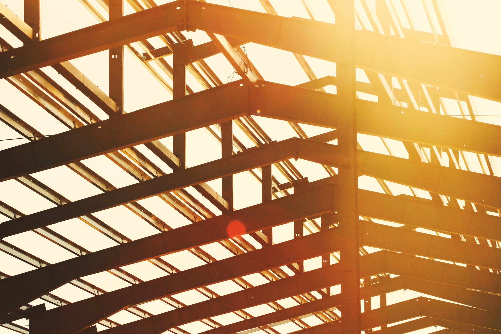 Sunlight shining through the unfinished, steel frame of an under construction building.