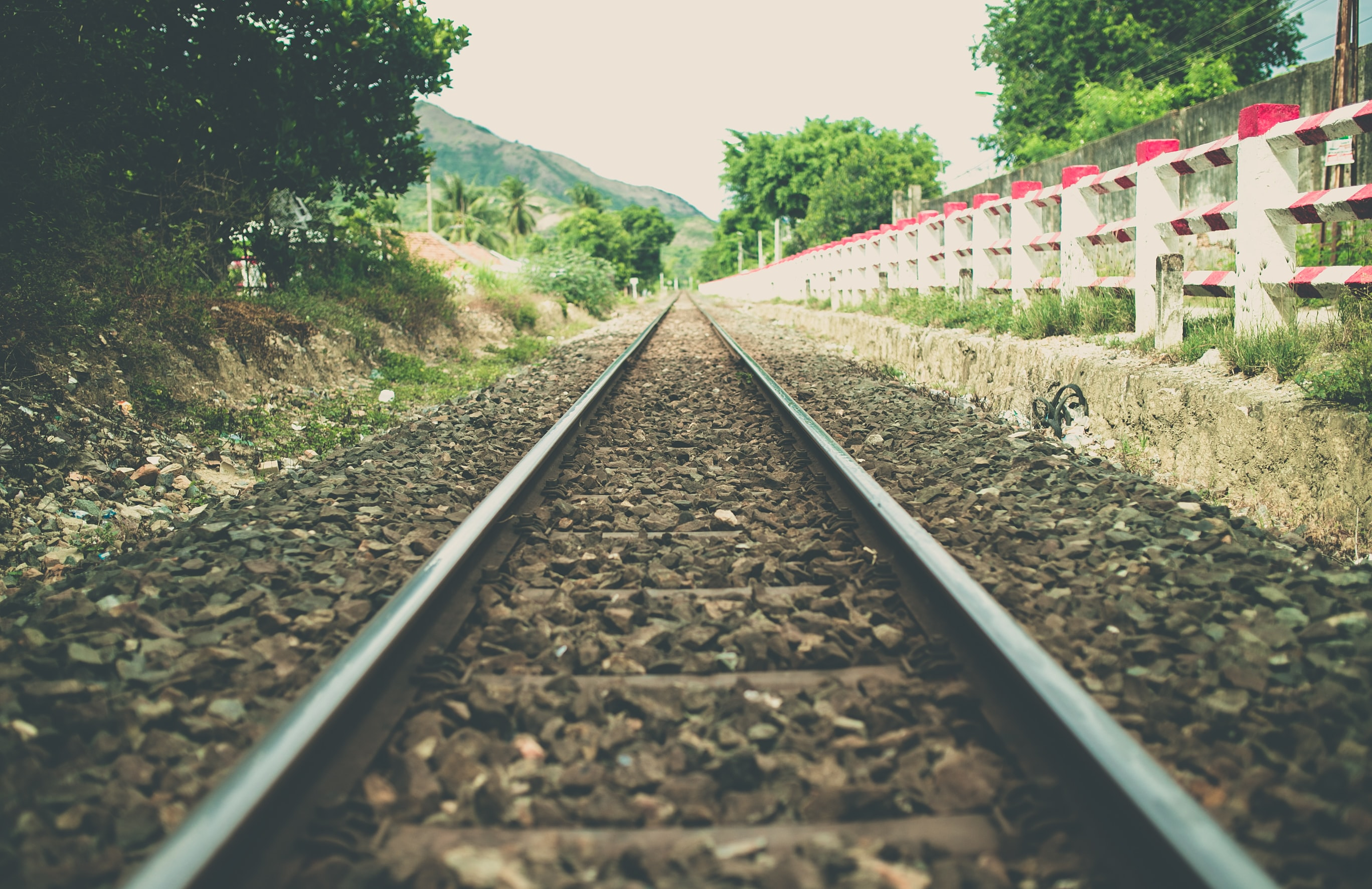 A perspective shot of a railroad track running down a path beside a red and white striped fence, several trees, and a mountain.