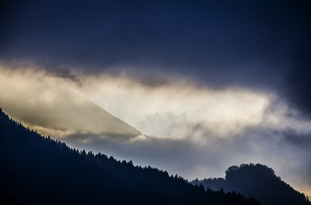 silhouette of mountain under clouds