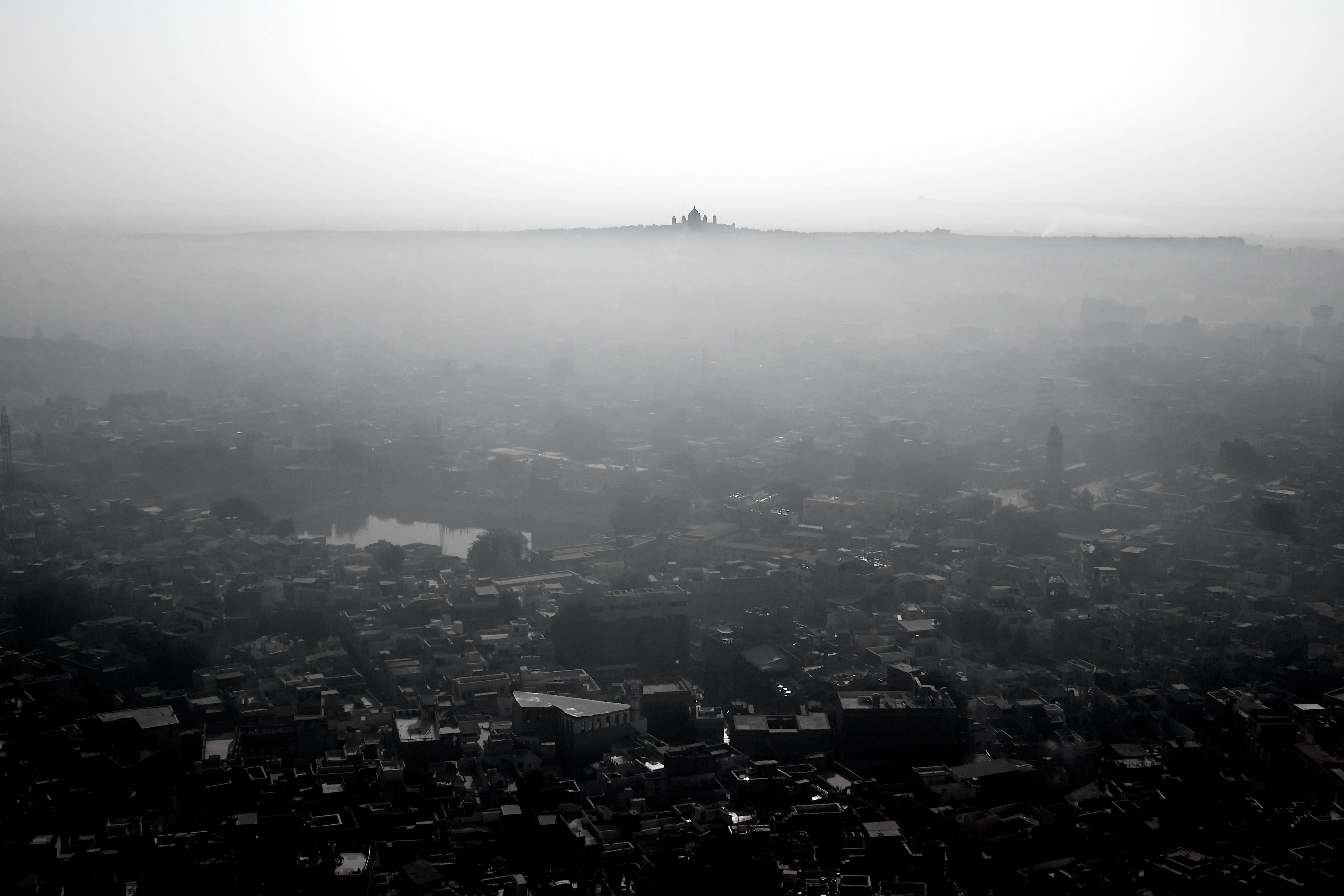 Black and white shot of city with haze and Taj Mahal on the horizon