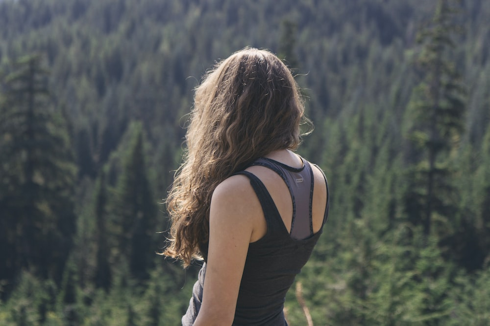woman standing while watching green trees at daytime