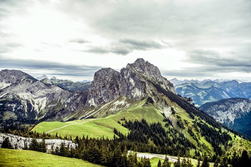 mountain covered by green grass and trees under white clouds