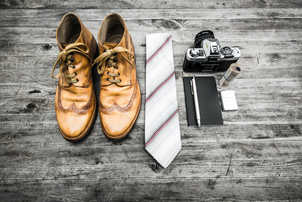 pair of brown leather boots beside necktie next to pen, notebook, and MILC camera