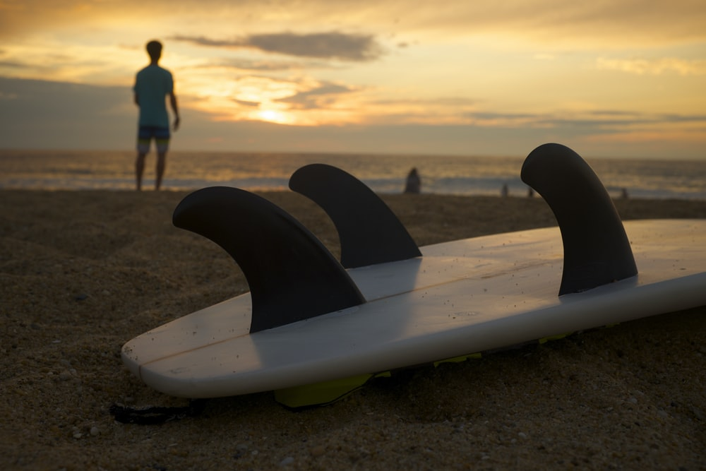 white and black surfboard on white sand during sunsetr