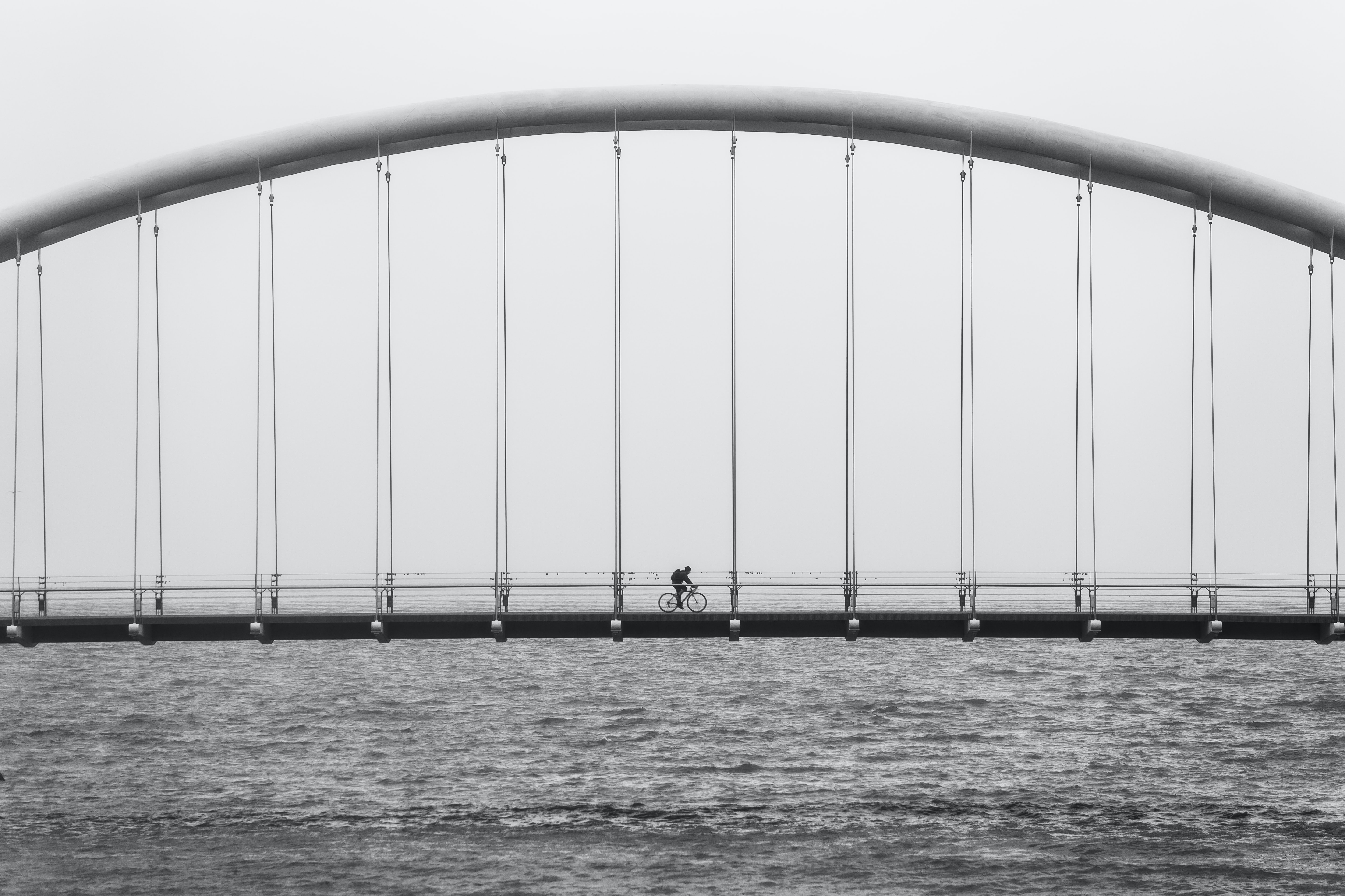 gray scale photo of person driving bike on bridge