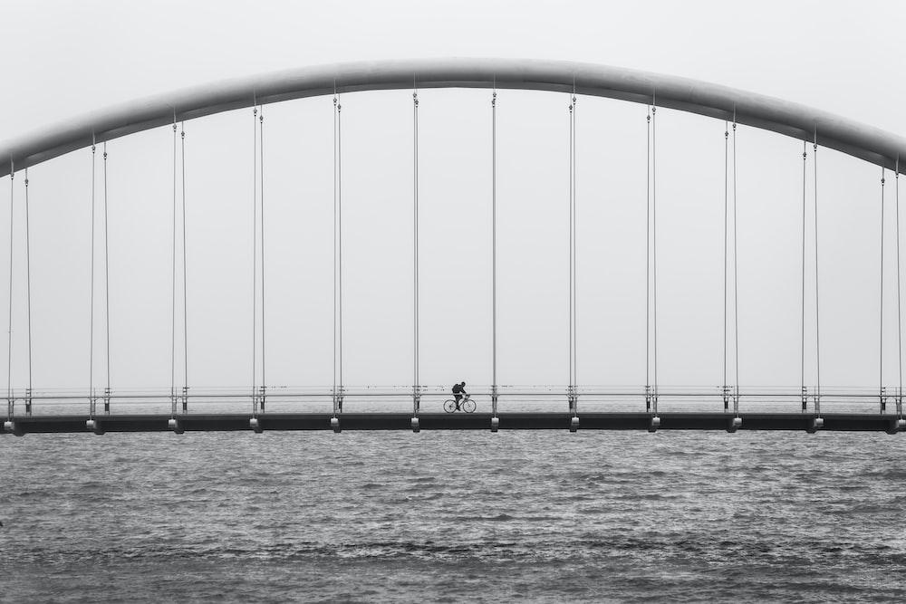 gray scale photo of person driving bike on bridge