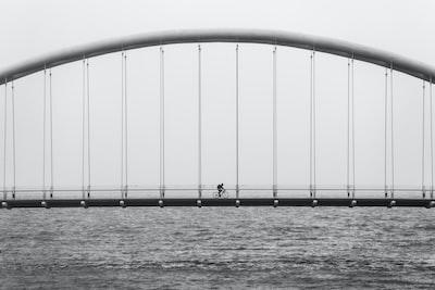 gray scale photo of person driving bike on bridge bridge teams background