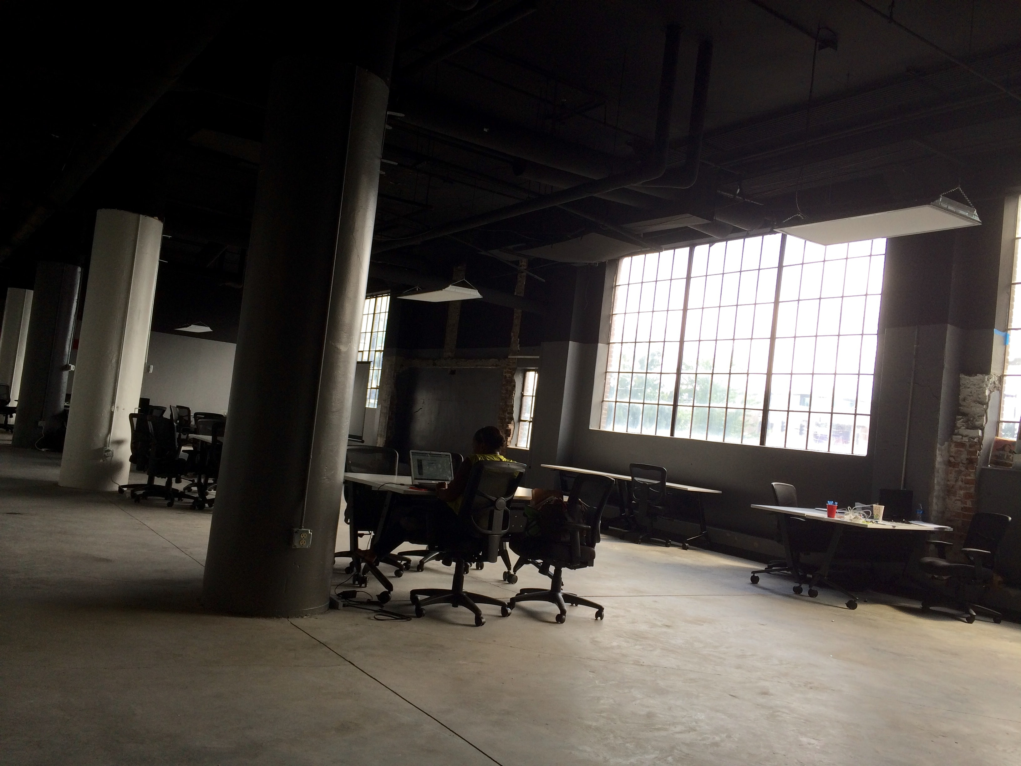 A lone employee working in a large loft office
