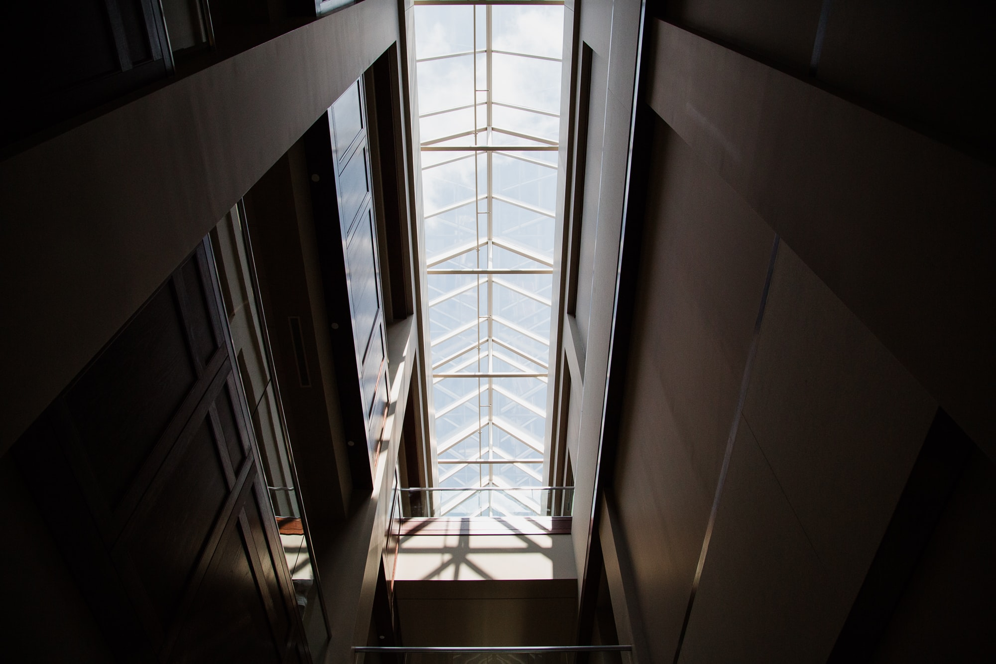 Looking up from a dark room at a building's roof with a long skylight with sunshine