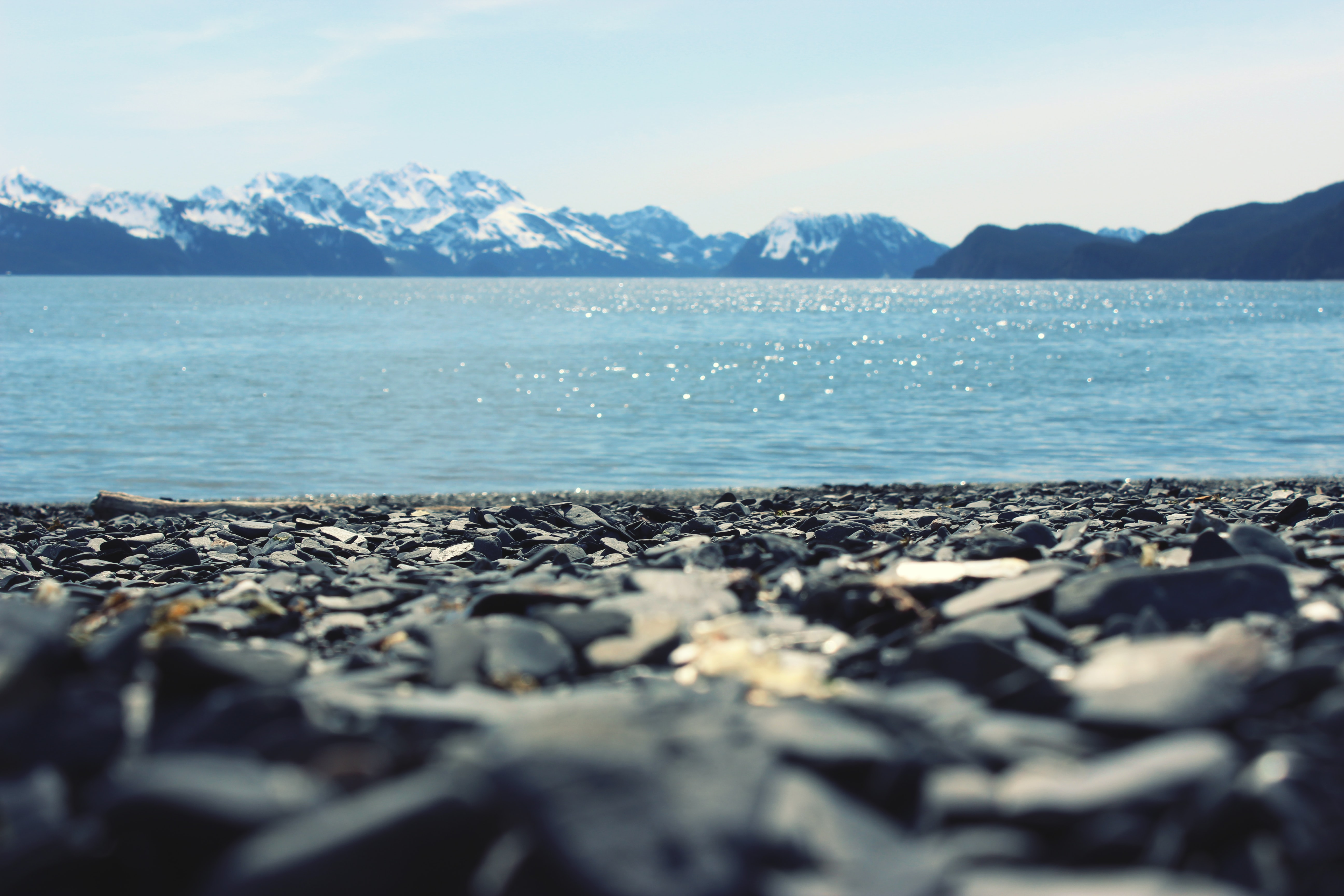 Snowy mountains on the horizon viewed from the rocky beach
