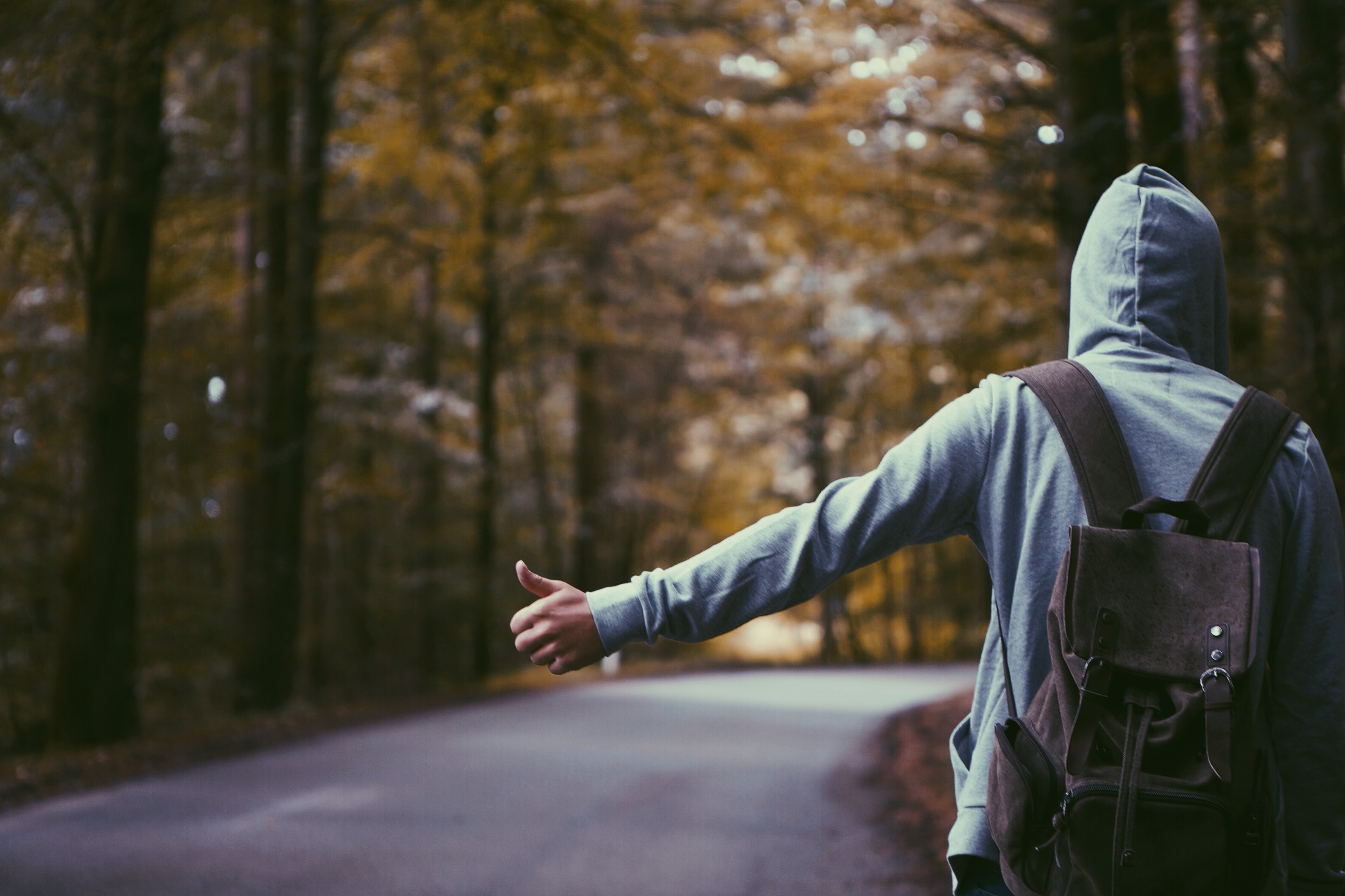 A hooded hitchhiker with a backpack extending his thumb on the side of an empty road