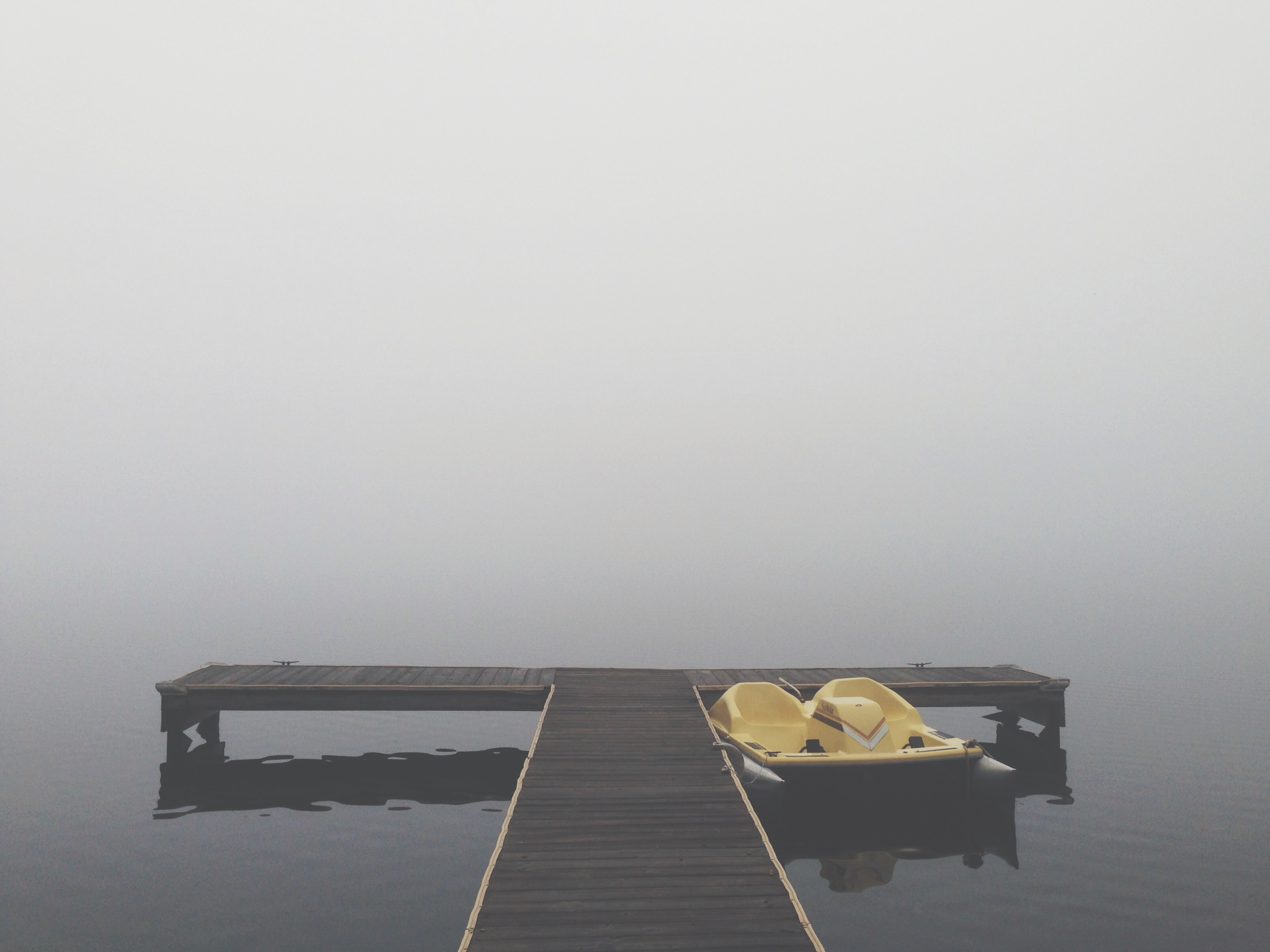 Empty wooden dock with paddle boat on a lake on a gray foggy day