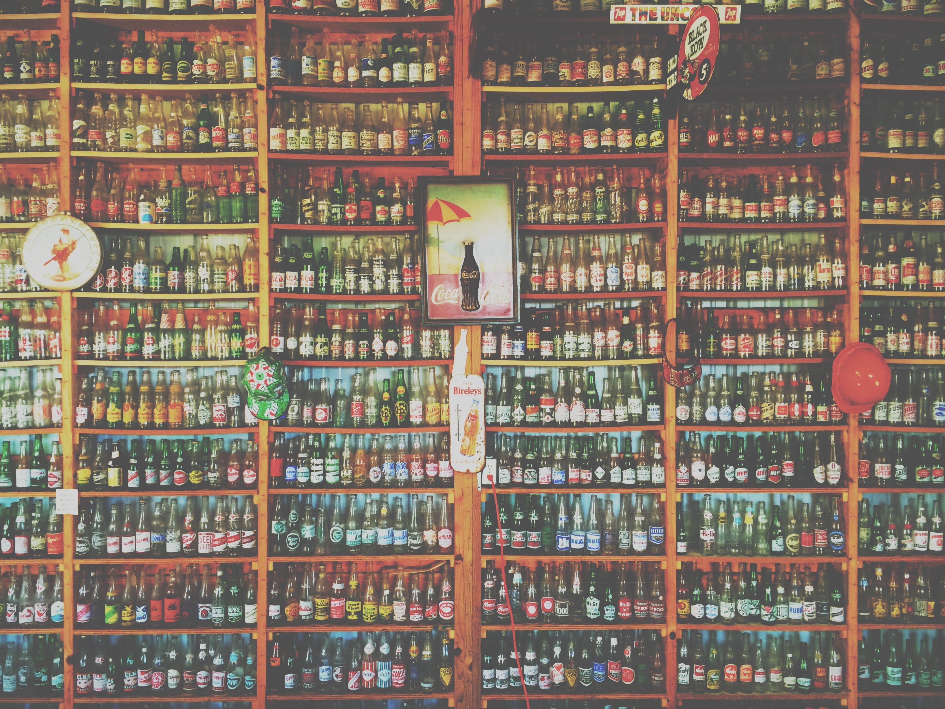 A collection of vintage Coca-Cola bottles on a large shelf.
